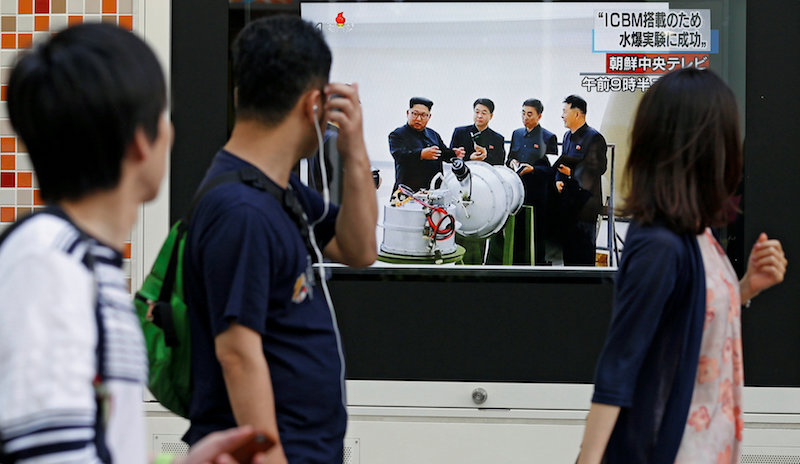 People walk past a street monitor showing North Korea's leader Kim Jong-Un in a news report about North Korea's nuclear test, in Tokyo
